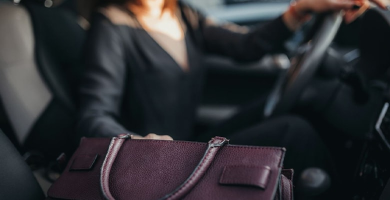 women on a car grabbing something from her bag